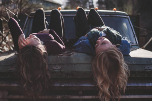 girls laying on a car bonnet